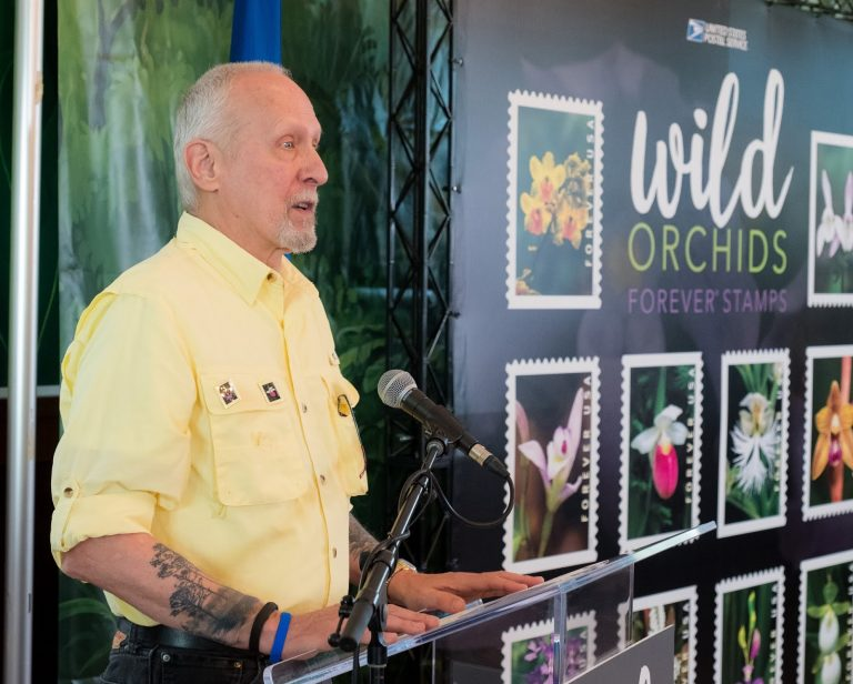 """CORAL GABLES, FL — The U.S. Postal Service celebrates the striking beauty of wild orchids with the release of the Wild Orchids Forever stamps. Part of the largest family of plants on Earth, orchids grow in many climates and thrive under a variety of conditions.The stamps were dedicated at the American Orchid Society Library at the Fairchild Tropical Botanic Garden, Coral Gables, FL. News about the stamps is being shared on social media using the hashtags #OrchidStamps and #FlowerStamps. Followers of the Postal Service's Facebook page can view video of the ceremony at facebook.com/usps.Art director Ethel Kessler designed the stamps with photographs taken by James A. Fowler.""""Orchids can be hard to find in a natural setting and today there is a conservation effort to preserve these beautiful flowers,"""" said Jakki Krage Strako, chief customer and marketing officer and executive vice president, U.S. Postal Service, who served as the event's dedicating official. """"Each of these stamps represent a masterpiece of nature that blossoms with color. They also continue the Postal Service tradition of showcasing the natural beauty of flowers on stamps.""""Joining Strako to dedicate the stamps were Georgia Tasker, author, horticulture writer and Pulitzer Prize finalist; Susan Wedegaertner, president, American Orchid Society; photographer James A. Fowler; and Lawrence Zettler, director of the orchid recovery program, Illinois College.""""Orchids are the world's most familiar group of flowers and these charming stamps showcase nine of the over 200 orchid species native to the United States,"""" said Zettler. """"These stamps also serve as a reminder of their beauty and their vulnerability.""""Each stamp features a photograph of one of these nine species: Cypripedium californicum, Hexalectris spicata, Cypripedium reginae, Spiranthes odorata, Triphora trianthophoros, Platanthera grandiflora, Cyrtopodium polyphyllum, Calopogon tuberosus and Platanthera leucophaea. The booklet contains 10 stamp designs """